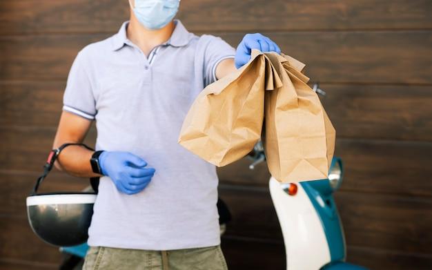Le livreur livre la nourriture au client par son cyclomoteur