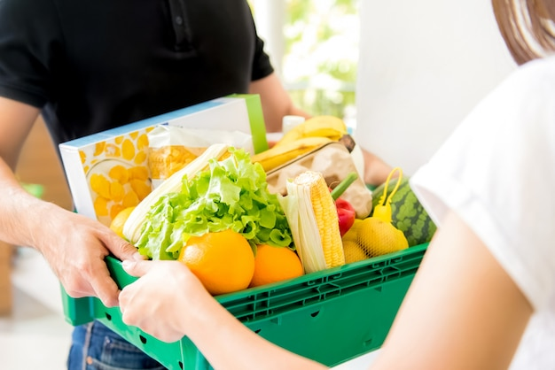 Livreur livrer de la nourriture à une femme à la maison