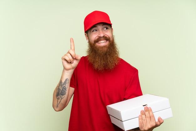Livreur avec une longue barbe sur fond vert isolé visant à réaliser la solution tout en levant un doigt