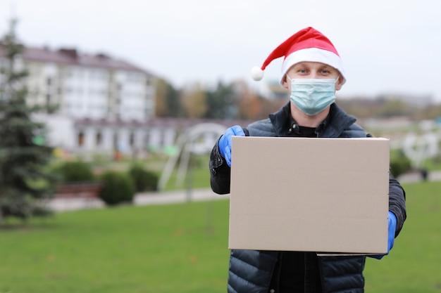 Livreur en masque de protection, gants et chapeau de père noël tenant la boîte dans les mains à l'extérieur, service de livraison pendant le coronavirus en période de vacances
