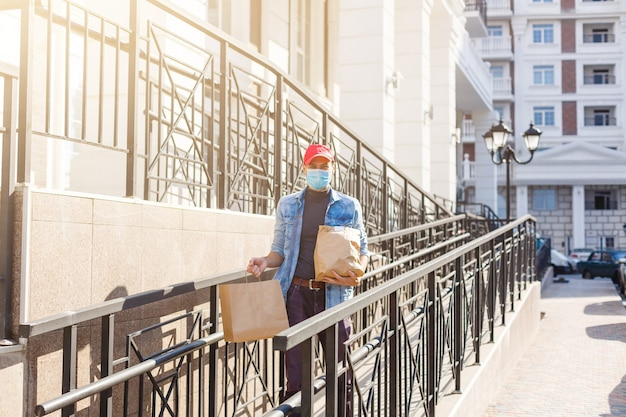 Livreur en masque de protection près de la maison du client, à l'extérieur