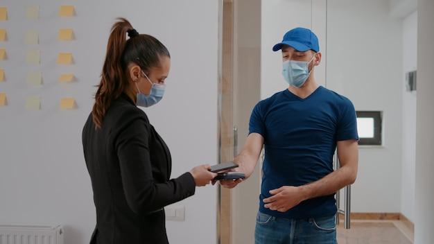Livreur avec masque de protection tenant un terminal de point de vente livrant une commande de plats à emporter