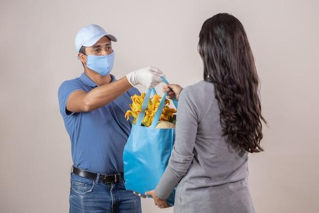 Livreur mexicain avec masque et gants livraison à domicile par quarantaine