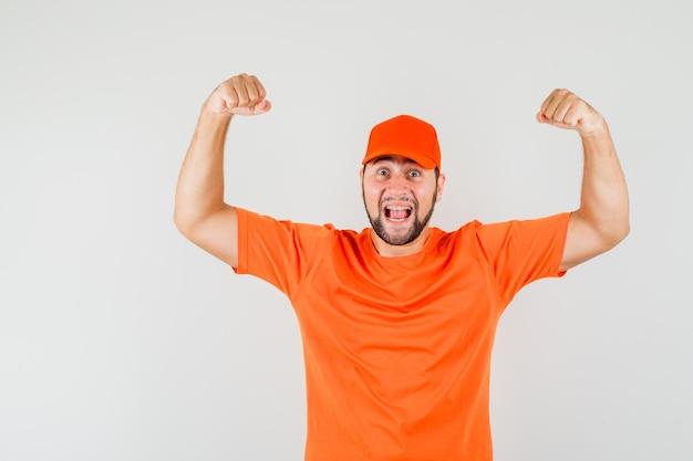 Livreur montrant un geste de réussite en t-shirt orange, casquette et à la félicité, vue de face.