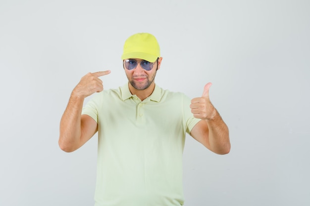Livreur montrant le pouce vers le haut en pointant sur des lunettes en uniforme jaune et regardant fier, vue de face.