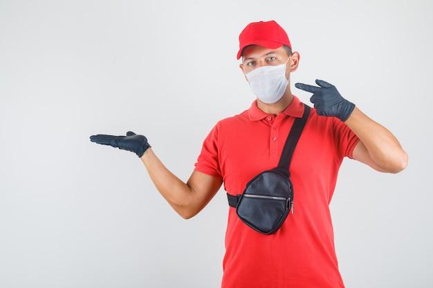 Livreur montrant quelque chose en uniforme rouge, masque médical, gants