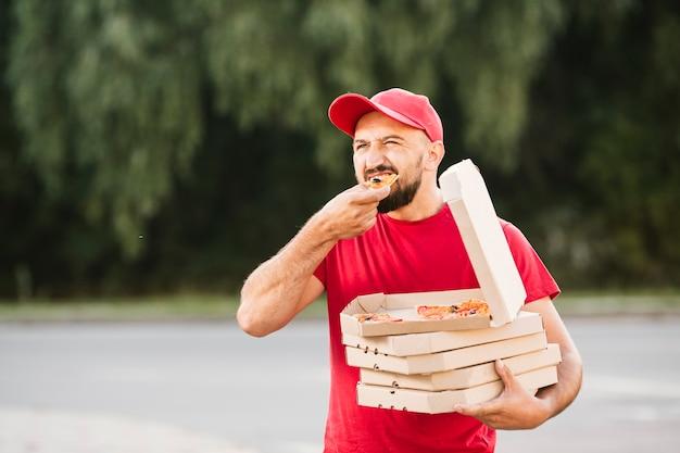 Livreur à moyen coup mangeant une pizza