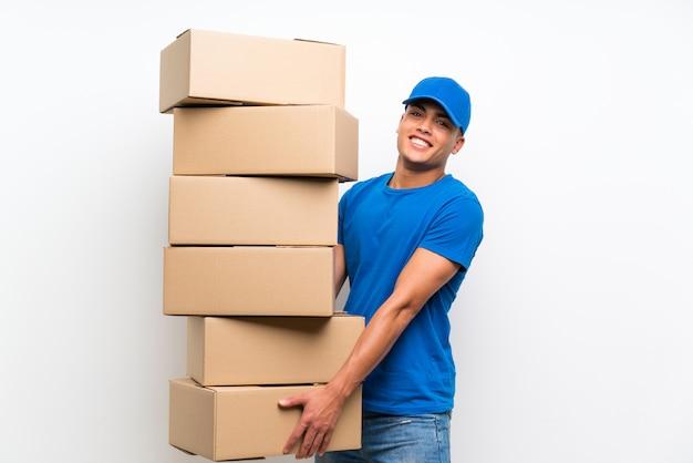 Livreur sur un mur blanc isolé avec beaucoup de boîtes