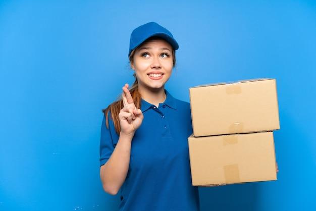 Livreur sur un mur bleu isolé avec les doigts qui se croisent et qui souhaitent le meilleur
