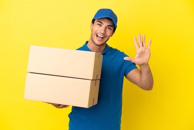 Livreur sur un mur jaune isolé comptant cinq avec les doigts