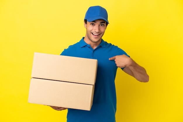 Livreur sur un mur jaune isolé avec une expression faciale surprise