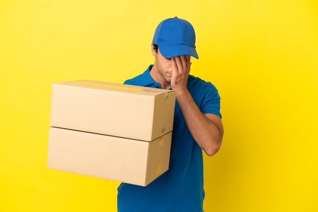 Livreur sur un mur jaune isolé avec une expression fatiguée et malade
