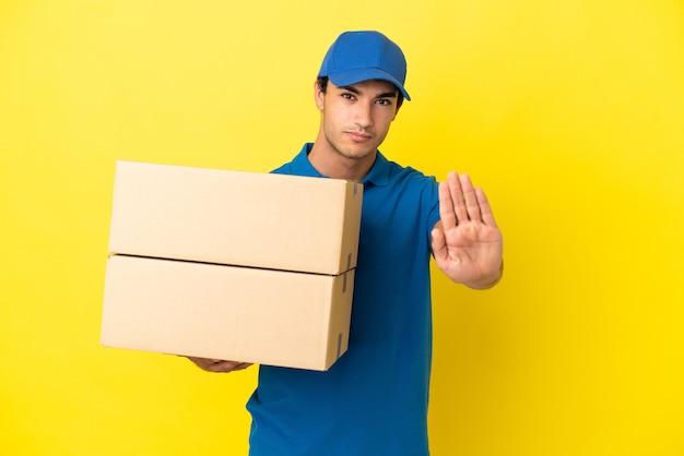 Livreur sur un mur jaune isolé faisant un geste d'arrêt