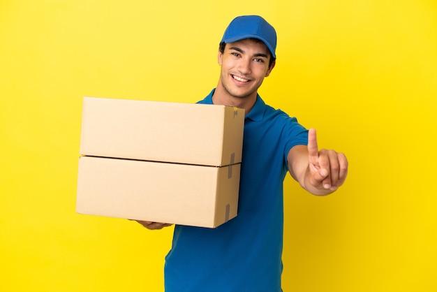 Livreur sur un mur jaune isolé montrant et levant un doigt