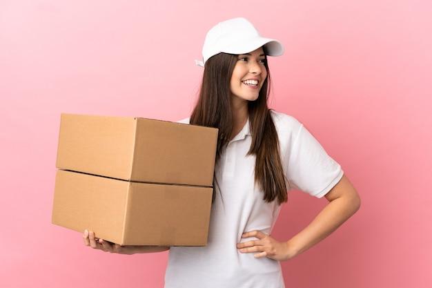Livreur sur un mur rose isolé posant avec les bras à la hanche et souriant