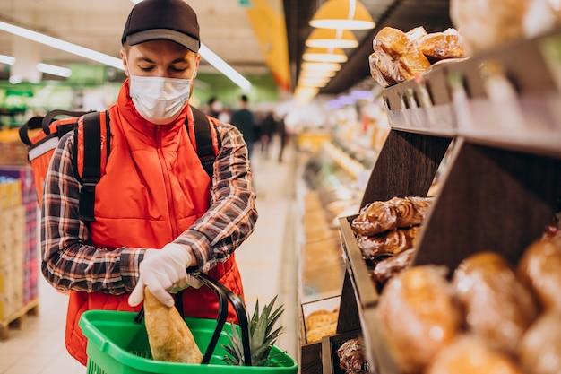 Livreur de nourriture achetant des produits à l'épicerie