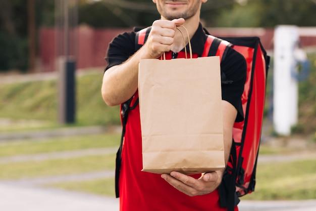 Livreur de nourriture commande d'un restaurant beau jeune homme dans un t-shirt et une casquette bonne livraison
