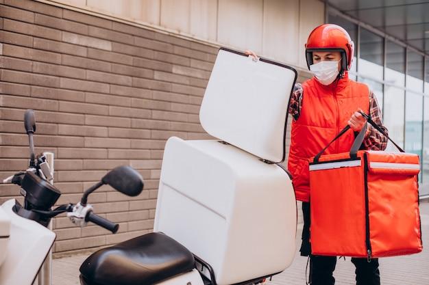 Livreur de nourriture conduisant un scooter avec une boîte avec de la nourriture et portant un masque