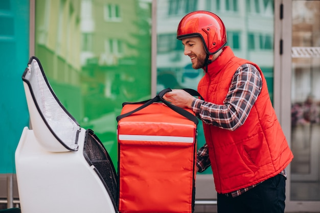 Livreur de nourriture livrant de la nourriture sur scooter