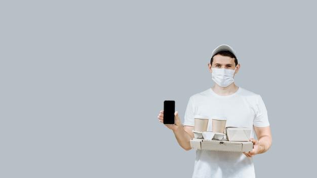 Un livreur de nourriture masqué et ganté a apporté une pizza et du café sur un fond gris