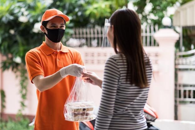 Un livreur de nourriture par coursier avec masque et gants près de la moto livre une boulangerie à une cliente avec un écran facial. commandez en ligne par application mobile. nouvelle activité normale pendant la pandémie delta de covid-19.