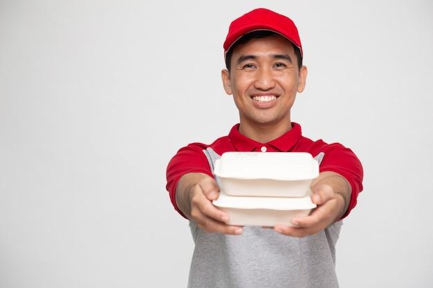 Livreur de nourriture tenant une boîte de nourriture isolé sur fond blanc
