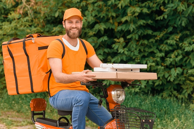Livreur de nourriture en uniforme orange assis sur un cyclomoteur