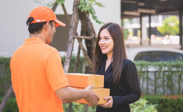 Livreur en orange apportant la femme au colis