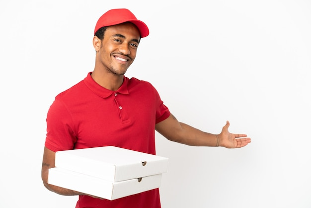 Un livreur de pizza afro-américain ramassant des boîtes de pizza sur un mur blanc isolé tendant les mains sur le côté pour inviter à venir