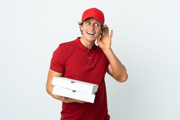 Livreur de pizza sur blanc en écoutant quelque chose en mettant la main sur l'oreille