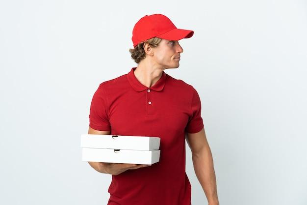 Livreur de pizza sur blanc à la recherche sur le côté
