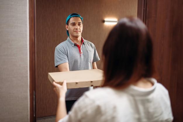 Livreur de pizza donne une boîte à une cliente