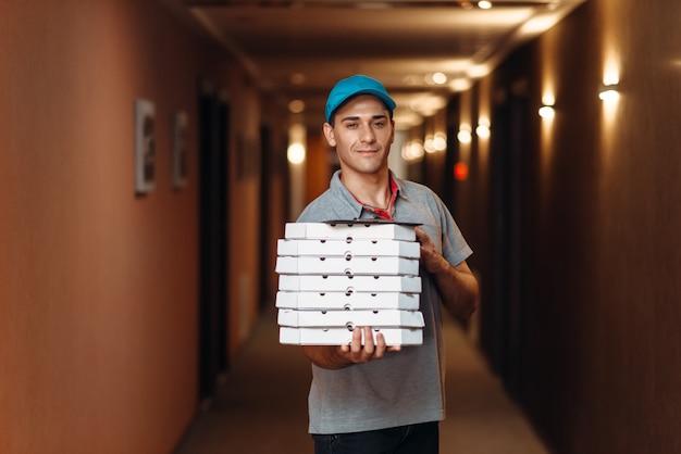 Livreur avec pizza fraîche dans des boîtes en carton