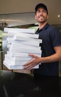 Livreur de pizza gai tenant de nombreuses boîtes à pizza