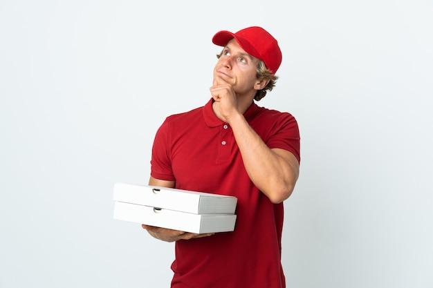 Livreur de pizza sur mur blanc isolé et levant