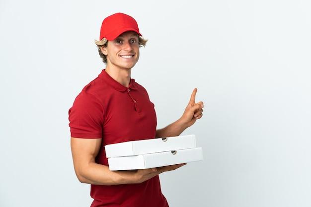 Livreur de pizza sur mur blanc isolé pointant vers l'arrière