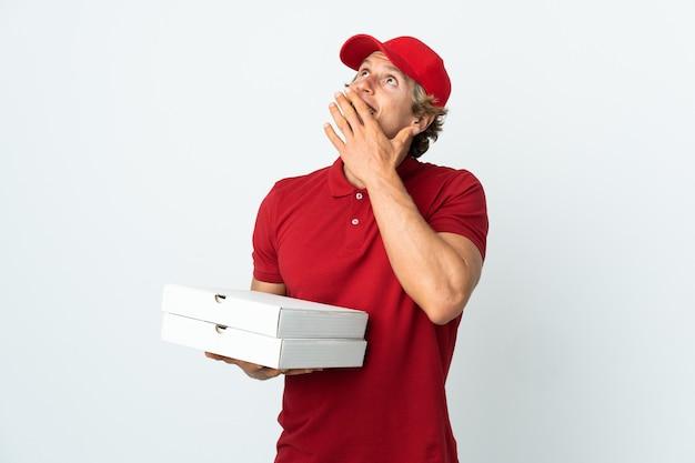 Livreur de pizza sur mur blanc isolé regardant en souriant