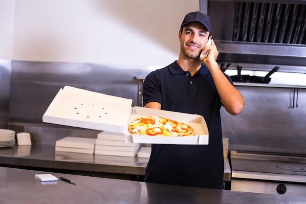 Livreur de pizza prenant une commande par téléphone