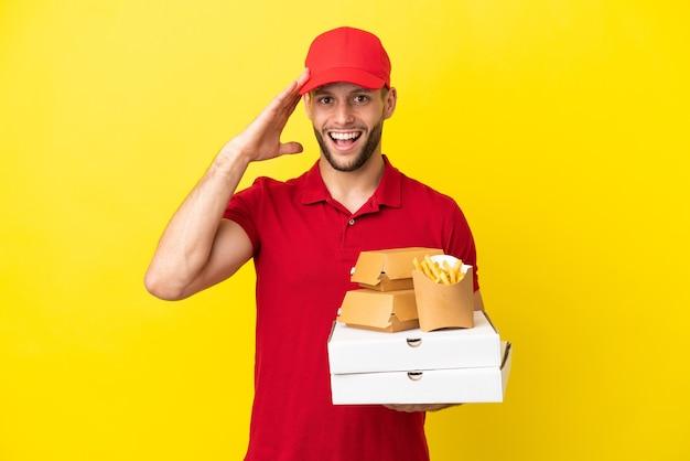 Livreur de pizza ramasser des boîtes de pizza et des hamburgers sur fond isolé avec une expression de surprise