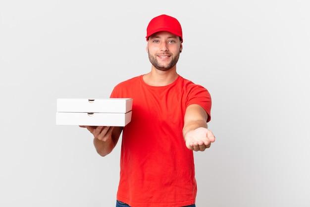 Livreur de pizza souriant joyeusement avec amical et offrant et montrant un concept