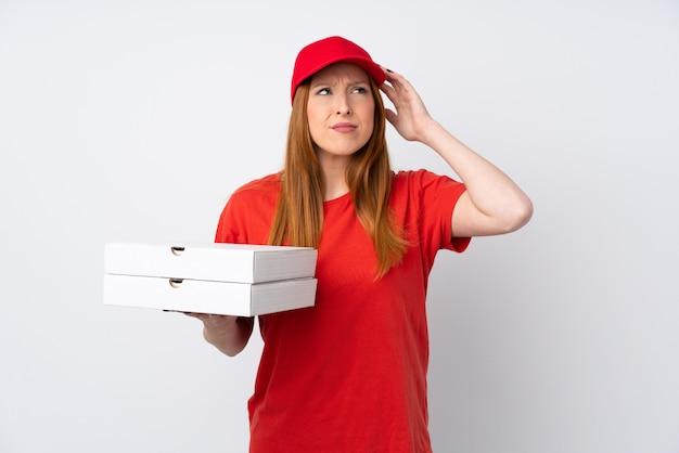 Livreur de pizza tenant une pizza sur un mur rose isolé ayant des doutes et avec une expression de visage confuse