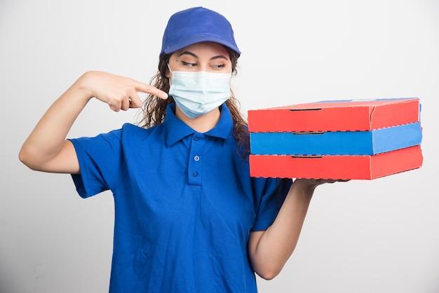 Livreur de pizza tenant trois boîtes avec un masque médical sur blanc