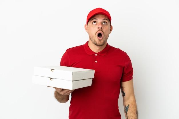 Livreur de pizza avec un uniforme de travail ramassant des boîtes de pizza sur un mur blanc isolé en levant et avec une expression surprise