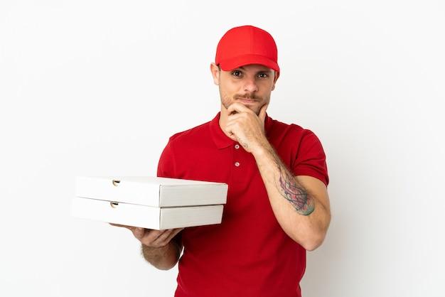 Livreur de pizza avec un uniforme de travail ramassant des boîtes de pizza sur un mur blanc isolé pensant