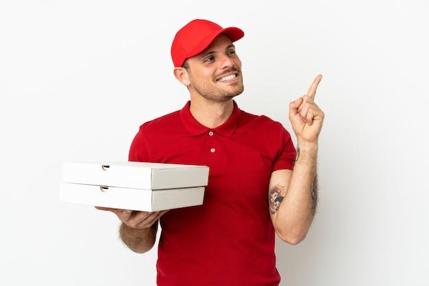 Livreur de pizza avec un uniforme de travail ramassant des boîtes de pizza sur un mur blanc isolé pointant vers une excellente idée
