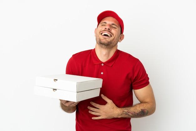 Livreur de pizza avec un uniforme de travail ramassant des boîtes de pizza sur un mur blanc isolé souriant beaucoup