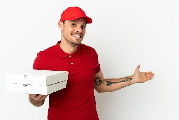 Livreur de pizza avec uniforme de travail ramassant des boîtes de pizza sur un mur blanc isolé tendant les mains sur le côté pour inviter à venir