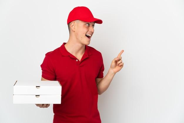 Livreur de pizza avec l'uniforme de travail ramasser des boîtes de pizza isolé sur blanc dans l'intention de réaliser la solution tout en levant un doigt vers le haut