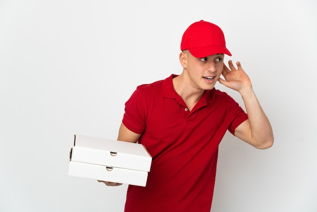 Livreur de pizza avec uniforme de travail ramasser des boîtes de pizza isolé sur un mur blanc à l'écoute de quelque chose en mettant la main sur l'oreille