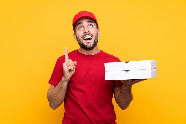 Livreur de pizza avec uniforme de travail ramasser des boîtes à pizza sur jaune isolé dans l'intention de réaliser la solution tout en levant un doigt